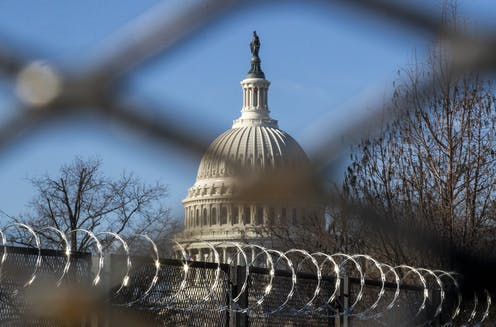 View of the US Capitol with barbed wire in the foreground.