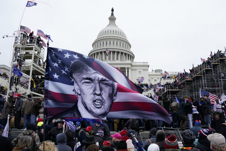 Crowd gathers with a large flag depicting Donald Trump with a Stars and Stripes background in front of the US Capitol Building.