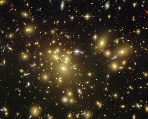 A collection of galaxies captured by the Hubble Telescope showing strong lensing as light is bent into a circular shape.