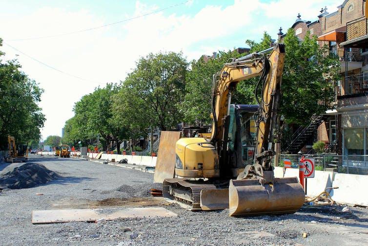An excavator on an urban tree-lined street