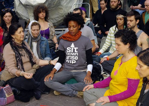 """People sit on the ground and meditate. One t-shirt reads, """"I sit down, I rise up.'"""