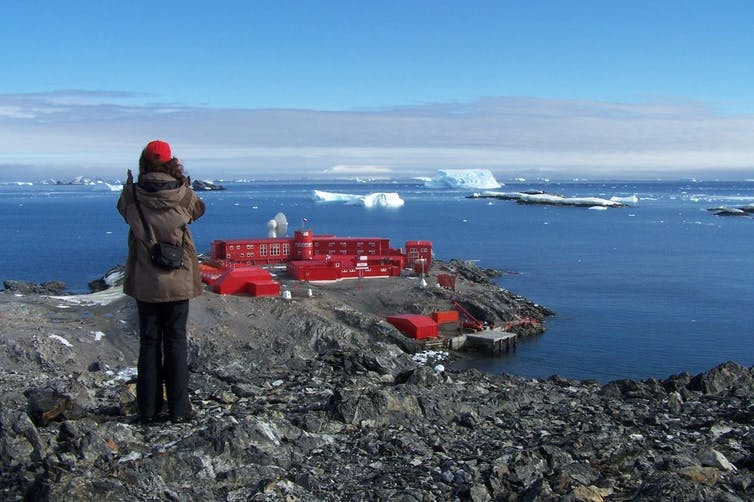 A person looking at the red research station in the distance, by the ocean