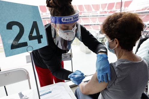 Person being vaccinated by a health worker in a stadium in the United States