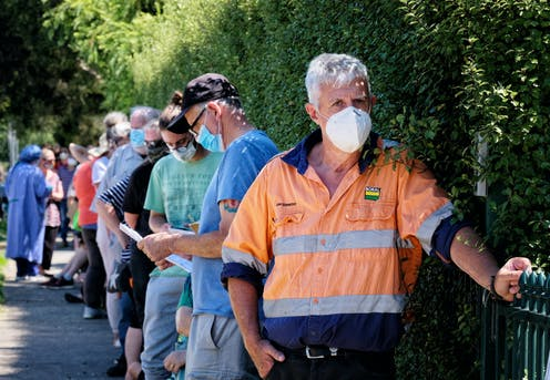 A queue of people await COVID testing in Melbourne.
