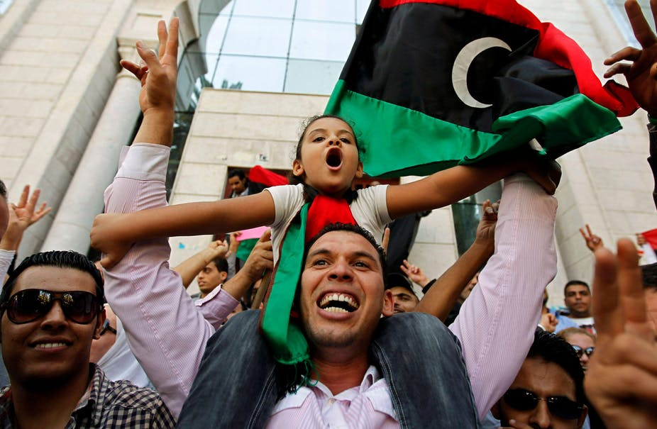 Smiling man with young girl on his shoulders with a Libyan flag in the background.