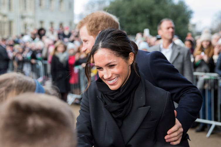 Meghan Markle greeting a crowd with her husband Prince Harry behind her.