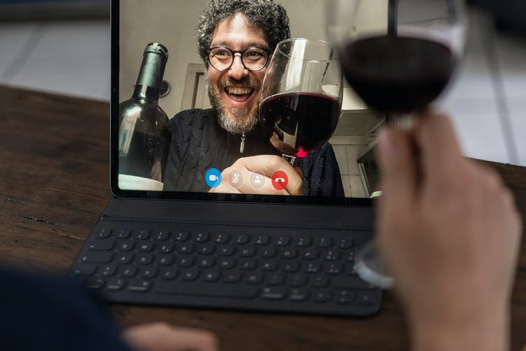 Two people on a videocall drinking red wine