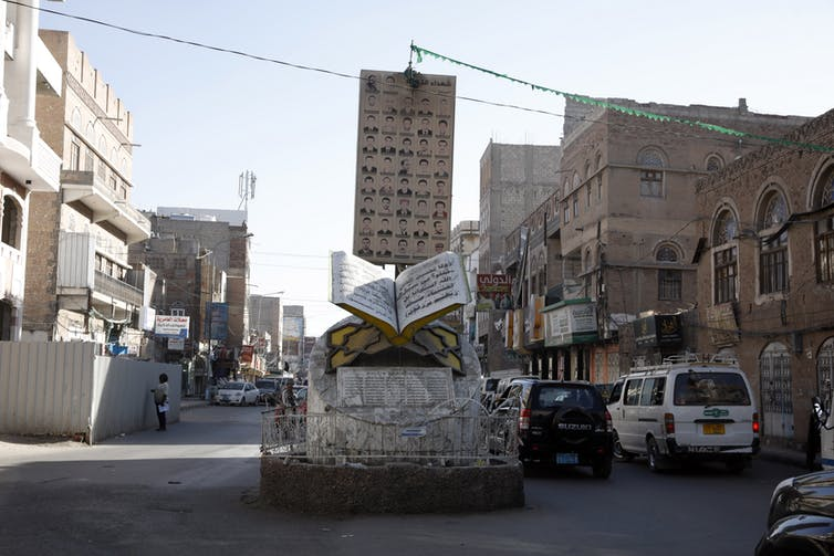 Cars drive past a memorial to the dead of the Yemen civil war in the capital Sana'a, January 2021.