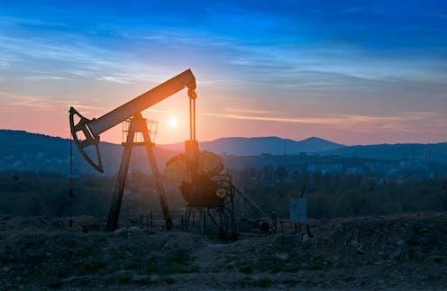 An oil derrick in a rocky field at sunset.