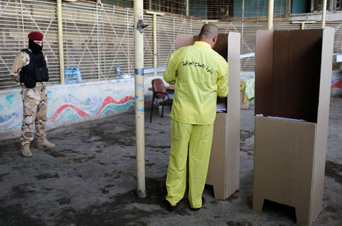 A man wearing a prison uniform casts a vote at a cardboard ballot booth.