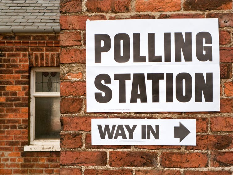 A sign directing people to a polling station stuck on a wall.