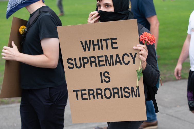 A person with a face covering holding a sign WHITE SUPREMACY IS TERRORISM