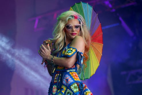 Drag queen on stage wearing a multi-coloured nitted dress and holding a rainbow umbrella