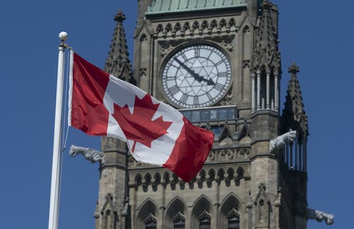 The Canadian flag flies in front of the Peace Tower at the Canadian parliament.