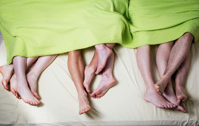 Six pairs of feet stick out from under a blanket.