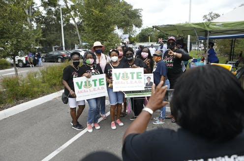 Several African American women pose for a photo while holding 'vote' signs.