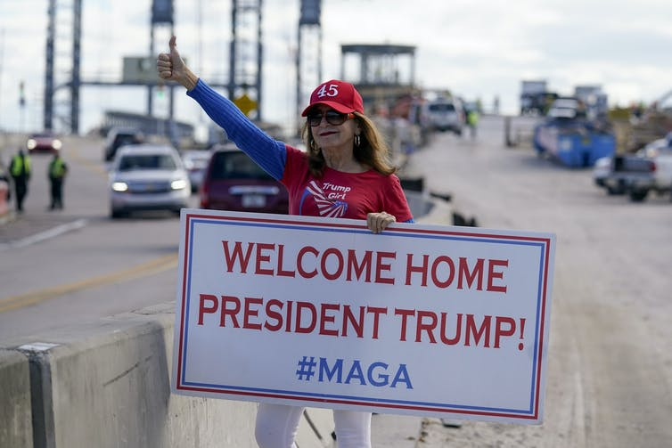 A woman holds a Welcome Home President Trump sign on a roadside.