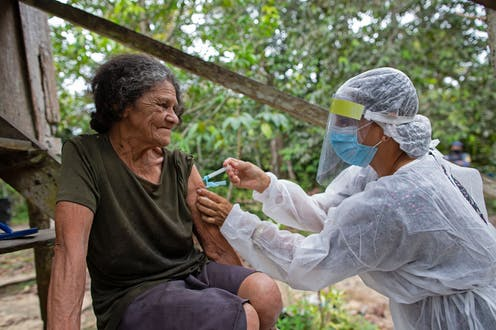 A Brazilian health worker administers a COVID-19 vaccine to an elderly woman.