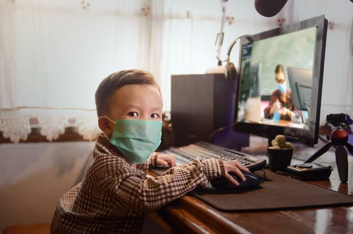 Child wearing face mask sits at computer