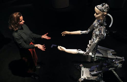A woman and a humanoid robot reach out to each other