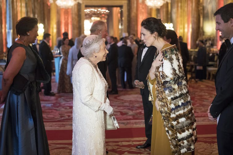 The queen and Jacinda Ardern who is wearing a traditional Māori cloak or