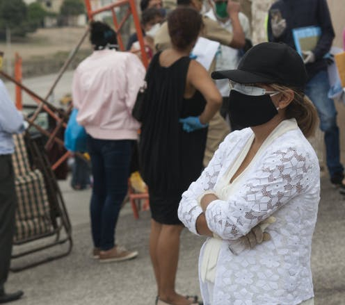 A woman wearing a cloth mask over a medical mask