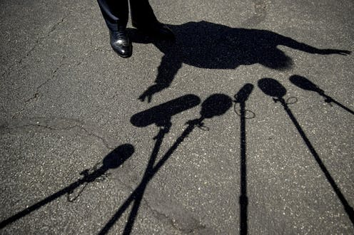 Trump's feet and his silhouette are seen surrounded by the shadows of microphones on asphalt.