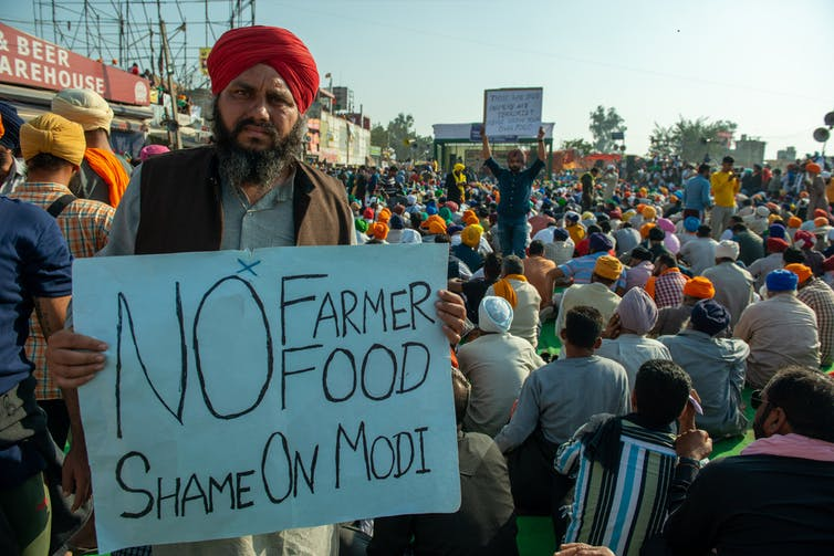 Man holds sign saying 'No farmer food. Shame on Modi'