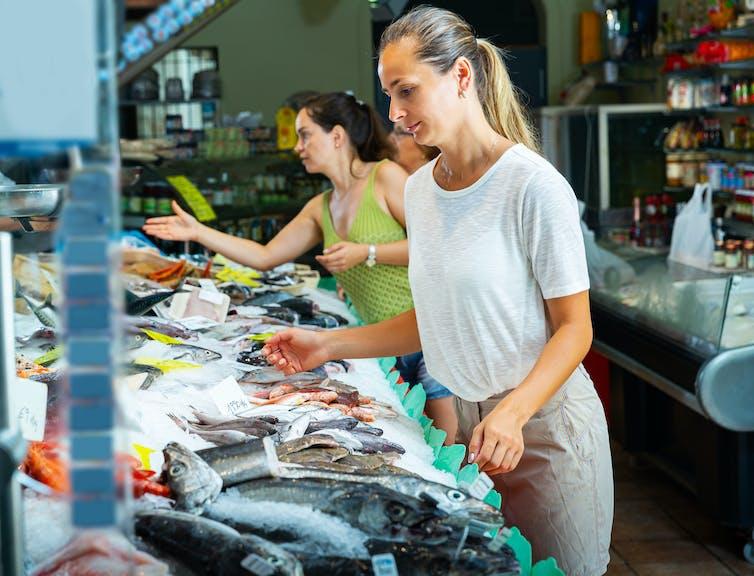 A woman surveys the produce at a fish market.