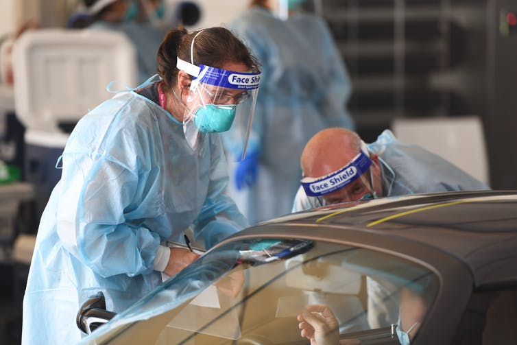 Two health-care workers conducting COVID testing at a drive-through site.