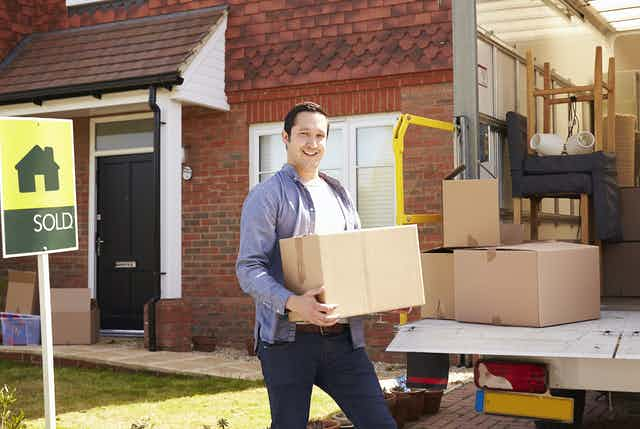 Man loading truck with household goods in front of sold house