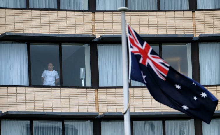 A hotel guest looks out from a window at the Holiday Inn at Melbourne Airport, Australia