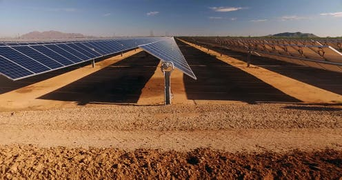 Three rows of solar panels in a desert viewed from the side.