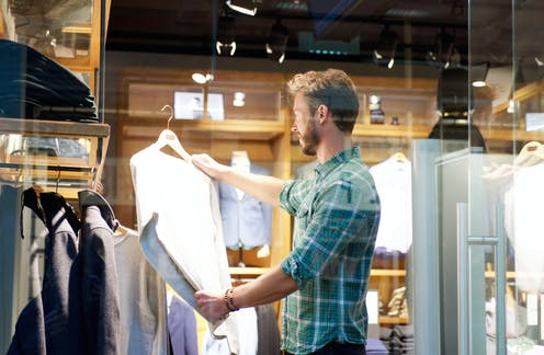 Man in shop looking at sweater on hanger