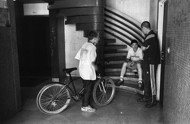 Des jeunes dans le hall d'un immeuble de la cité de la Grande Borne à Grigny, en juillet 2002.