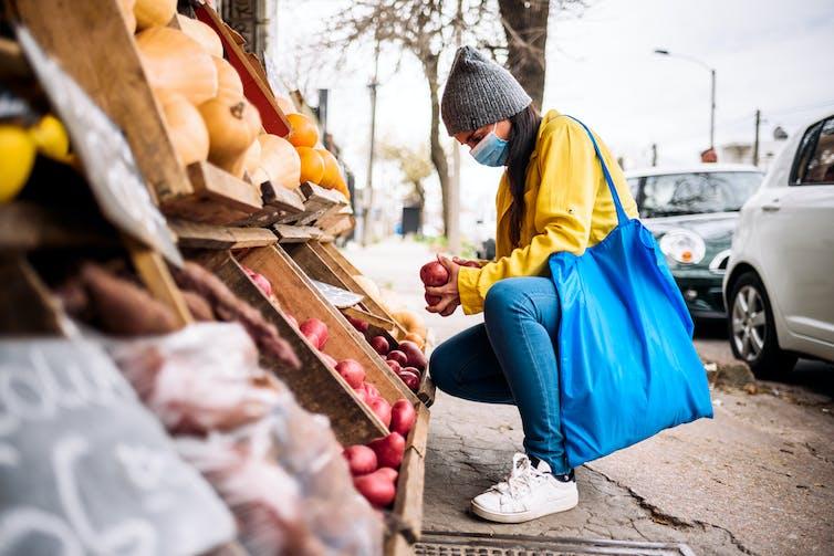Woman choosing vegetables at greengrocer