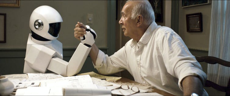 A robot and an elderly man arm wrestle on a table