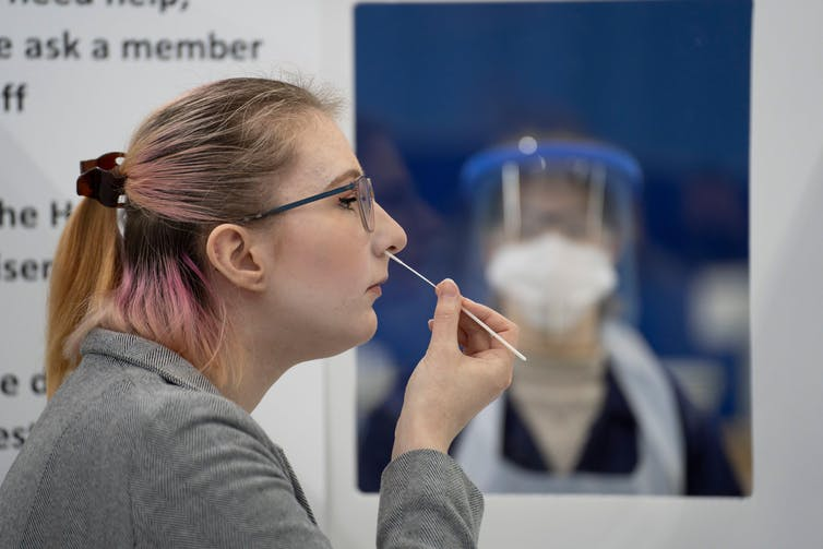 A person swabbing their nose for COVID.