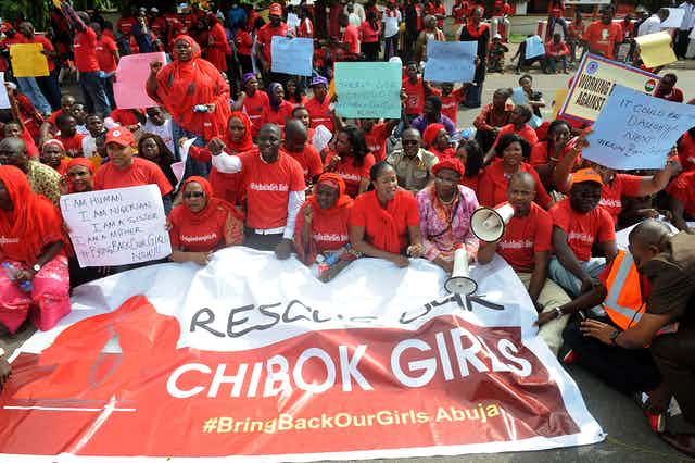 A group of people wearing red shirts and holding a large printed banner while protesting on the street of Abuja, Nigeria.