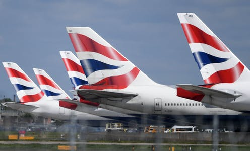 The tails of five British Airways planes in a row.