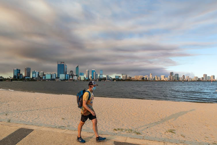 A man wearing a mask walks along a beach in Perth.