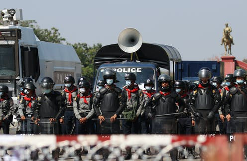 Myanmar police with security vehicles at a barricade to hold back protestors.