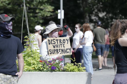 A man holding a sign that reads DESTROY WHITE SUPREMACY