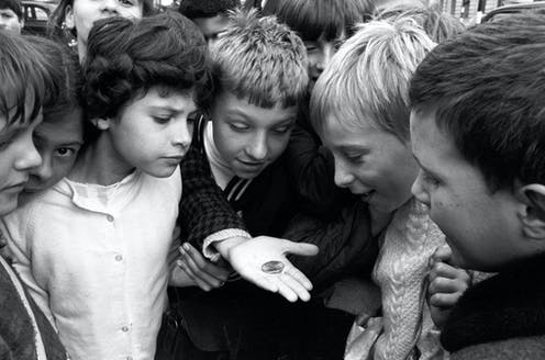 A photo from 1969 showing a group of children gathering to look at the new decimal 50 pence coin.