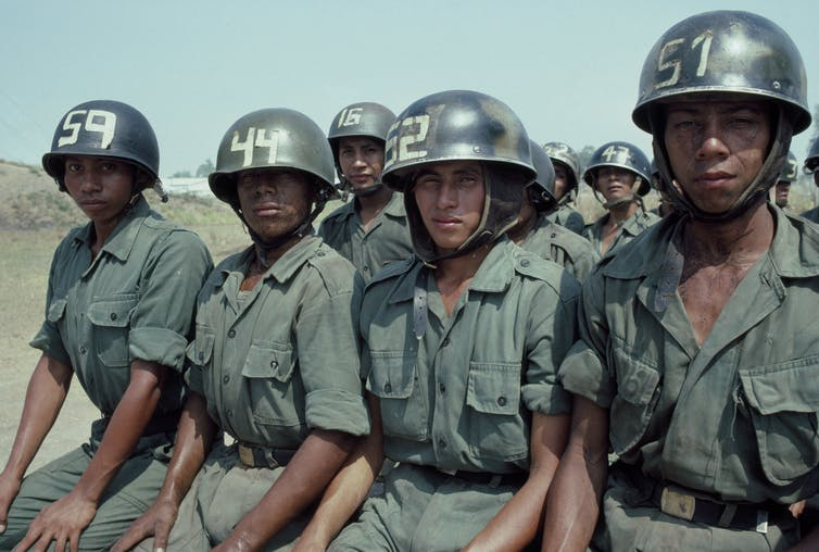Half a dozen young men in green military gear and helmets sit nervously and look straight at the camera