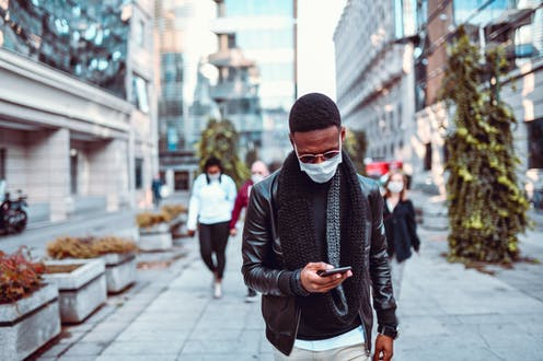 A man wearing a surgical mask walking down a city street looking at his phone