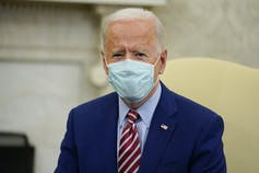 Biden wears a mask while sitting in the Oval Office.