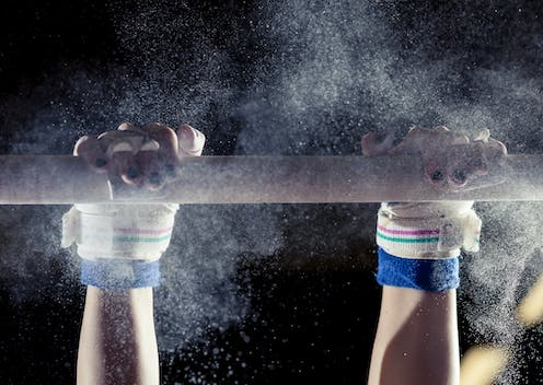 gymnast's hands on a bar with powder flying