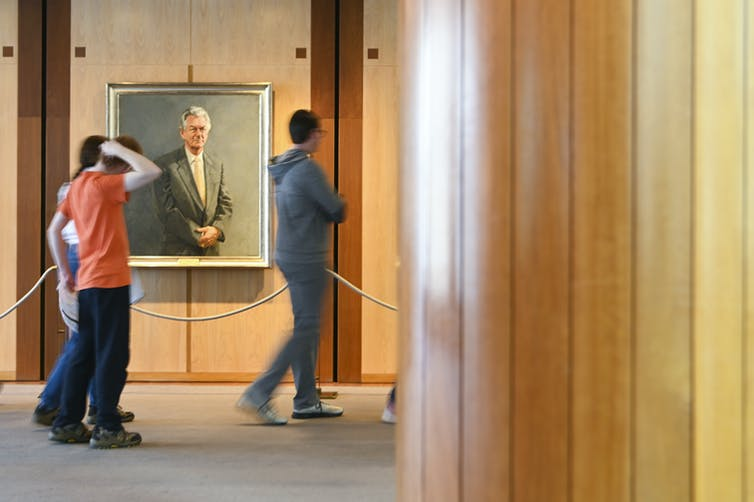 Three people walk past a portrait hanging in a wood-panelled room.