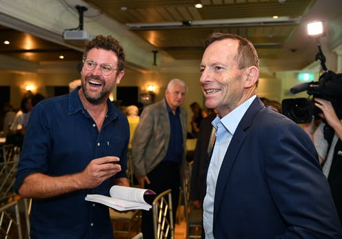 Johannes Leak signs a book for Tony Abbott during a book launch.